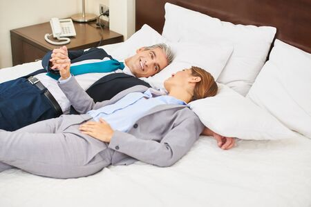eroticism: Happy business couple laying on bed in a hotel room and holding hands