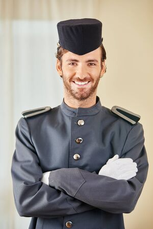 porter: Friendly hotel page in uniform smiling in a hotel room