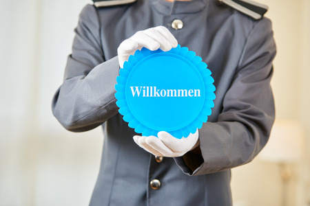 willkommen: Hotel clerk holding German badge saying Willkommen (welcome) in a hotel room