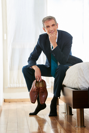 recreation room: Smiling business man sitting with his shoes in his hands in a hotel room