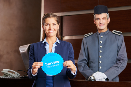 hospitality staff: Woman holding service guarantee sign in hotel with smiling concierge behind her