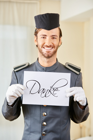 hospitality staff: Smiling hotel clerk holding German sign saying Danke (thanks) in hotel room