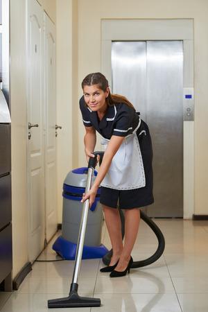 gospodarstwo domowe: Sprzątaczka w hotelu korytarzu z odkurzacza podczas sprzątania