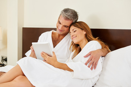 cuddle: Happy couple in hotel room cuddle with a tablet computer Stock Photo