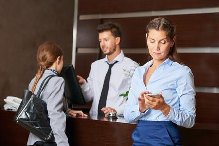 Conciërge bij de hotelreceptie serveren gasten met een vrouw die haar smartphone Stockfoto
