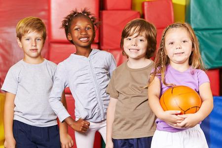 educacion fisica: Niños sonriendo equipo de pie con bola en un gimnasio de una escuela preescolar