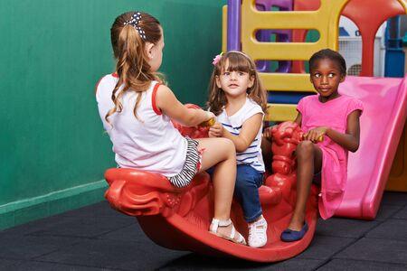 three children: Three children rocking on rocker together at an indoor playground Stock Photo