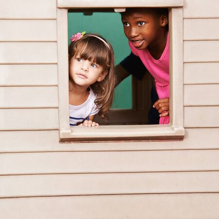 playhouse: Two girls playing together in a playhouse and looking through the window