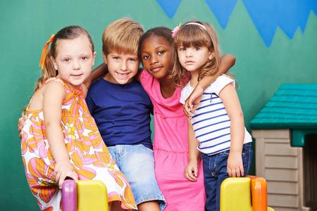 niños felices: Feliz grupo de niños que abrazan en un jardín de infancia