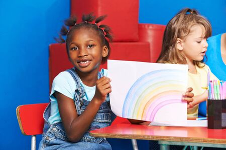 pedagogy: African girl with rainbow drawing on piece of paper in kindergarten
