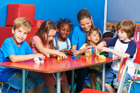 Los niños que juegan con un profesor de bloques de construcción juntos en edad preescolar