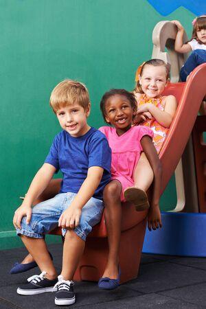 slide: Happy group of kids playing on slide in preschool
