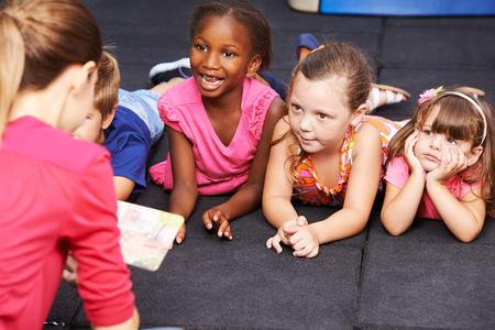 Des enfants heureux écoute livre de conte de fées dans l'enseignement préscolaire lus par puéricultrice