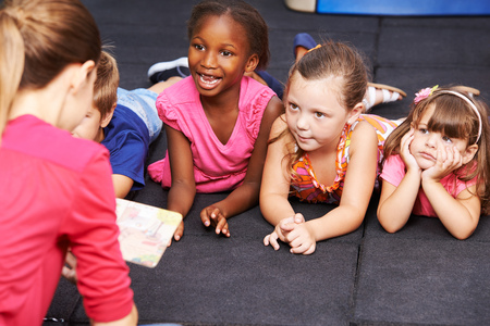 Glückliche Kinder zu Märchenbuch in der Vorschule hören von Erzieherin lesen Standard-Bild - 55605769