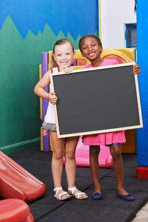 small girl: Two happy children holding a black chalkboard in preschool Stock Photo