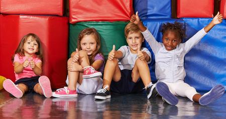 niños sentados: Feliz grupo de niños en edad preescolar gimnasio sosteniendo sus pulgares