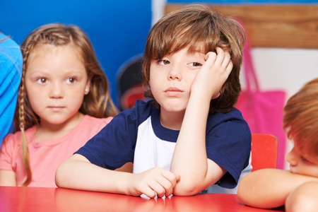saddened: Child is bored and sitting at table in kindergarten
