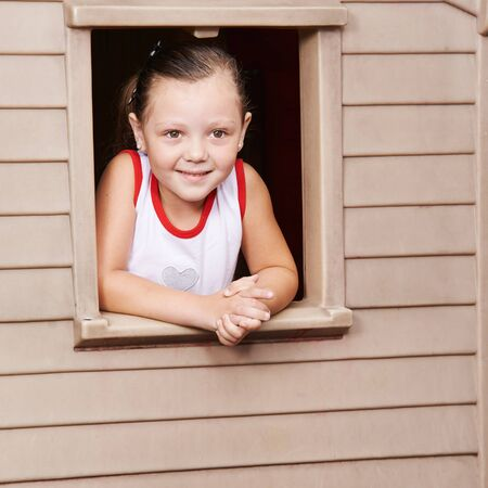 Happy girl looking through the window of a playhouse in kindergarten Stock Photo
