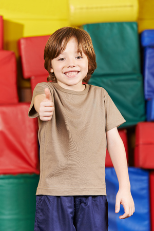 niño escuela: El muchacho feliz que detienen los pulgares en el gimnasio de la guardería Foto de archivo