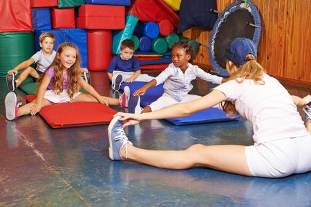 educacion fisica: Los niños que ejercen en la educación física con el profesor de educación física Foto de archivo