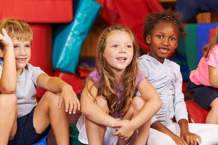 niños sentados: Feliz grupo de niños sentados juntos en un gimnasio de una escuela primaria