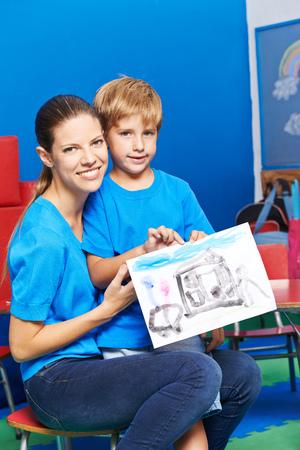 mama e hijo: sonriente madre e hijo feliz que muestra la pintura del color de agua en el jardín de infantes Foto de archivo