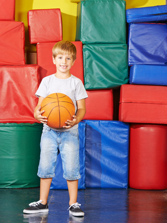 playschool: Smiling boy standing with basketball in gym of preschool Stock Photo