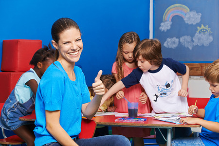 Nursery teacher holding thumbs up with group of children painting in the background Фото со стока