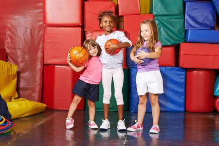 educacion fisica: Tres niñas felices de pie con bolas en un gimnasio de una escuela preescolar