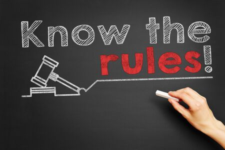 regulations: Hand writes Know the rules! on blackboard