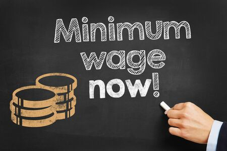 minimum wage: Hand writes Minimum wage now! on blackboard