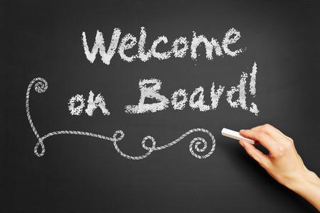 cordiality: Hand writes Welcome on board! on blackboard