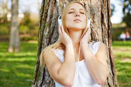 attractive woman: Young woman with headphones listening to music outside in a park