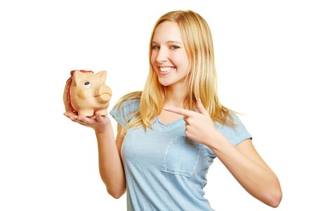 thrift box: Young smiling woman pointing to money in her piggy bank