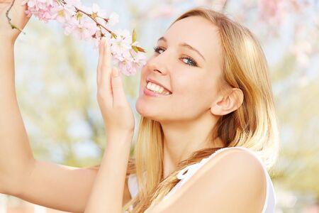 arbol de cerezo: Feliz chica rubia con olor aroma de flores de cerezo en primavera Foto de archivo