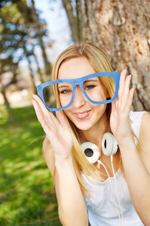 nearsighted: Young blonde woman with hipster nerd glasses in summer in a park