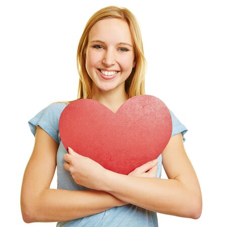 teen love: Girl embracing a big red heart as love symbol with her arms Stock Photo