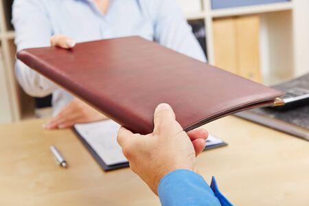 Mains de femme donnant portefeuille d'applications à l'homme des ressources humaines dans le bureau