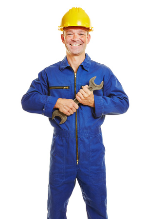 boiler suit: Smiling construction worker in boiler suit with safety helmet and jaw wrench