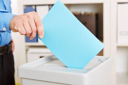 Hand met stembiljet een stemhokje tijdens verkiezingen
