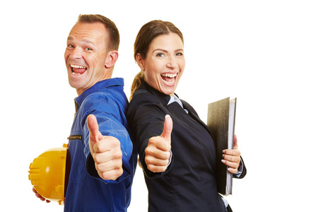 Happy worker and cheering businesswoman holding together their thumbs up
