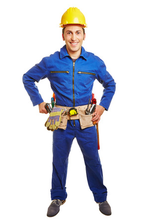 blue overall: Smiling worker with blue overall and hardhat and a tool belt