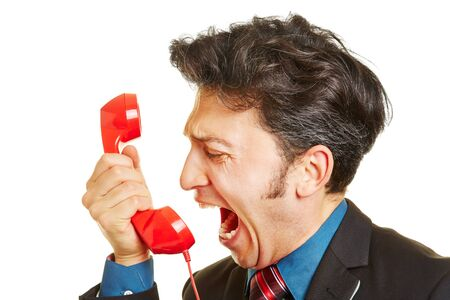 rant: Angry business man screaming loudly into a red phone receiver Stock Photo