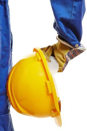 Hand of worker with yellow hardhat helmet