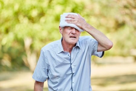Starszy mężczyzna o złym obiegu chłodzi głowę mokrą szmatką