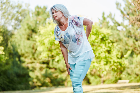 Old woman with back pain while walking in the nature in summer Stockfoto