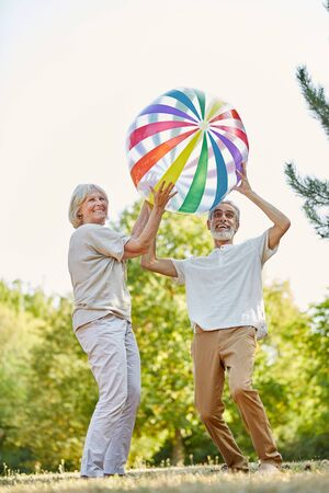 nonsense: Happy senior couple throwing a big ball on their holiday