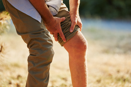 pangs: Old man with pain on the knee in the nature in summer