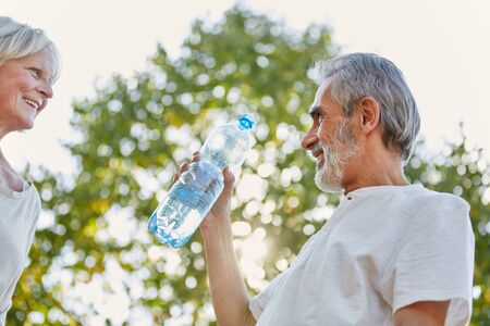 refreshment: Senior citizens drinking from a water bottle for refreshment in summer