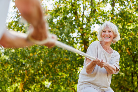 forceful: Happy senior woman playing tug of war with her husband in summer